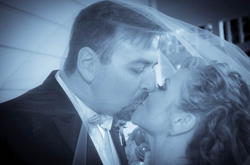 Bride and groom kissing on the porch at Camarillo Ranch House